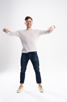 Bell'uomo con gli occhiali stupito e sorridente alla telecamera mentre presenta con la mano isolata su bianco