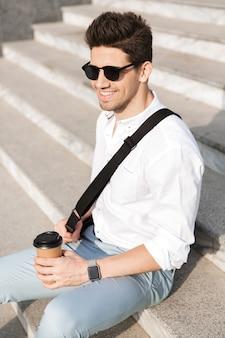 Bell'uomo che indossa occhiali da sole, beve caffè da asporto mentre è seduto sulle scale sulla strada della città