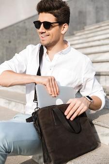 Bell'uomo che indossa occhiali da sole, mettendo il laptop nella sua borsa, mentre era seduto sulle scale sulla strada della città