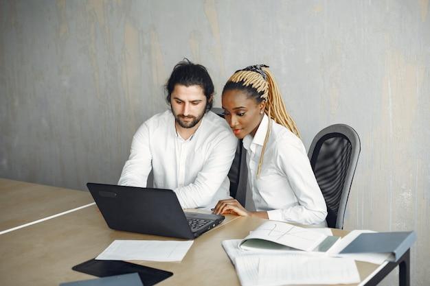 Bell'uomo in camicia bianca. donna africana con partner. ragazzo con un laptop.