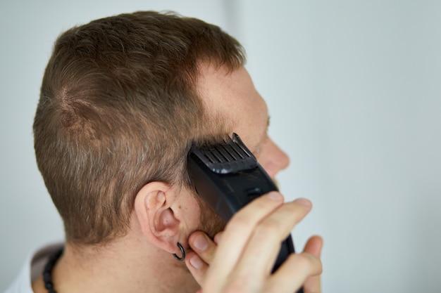 Uomo bello in barba taglio t-shirt bianca con trimmer a casa