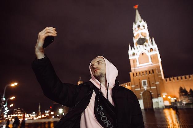 Uomo bello in una giacca a vento tenendo selfie durante la notte contro la torre spassky nella piazza rossa di mosca.