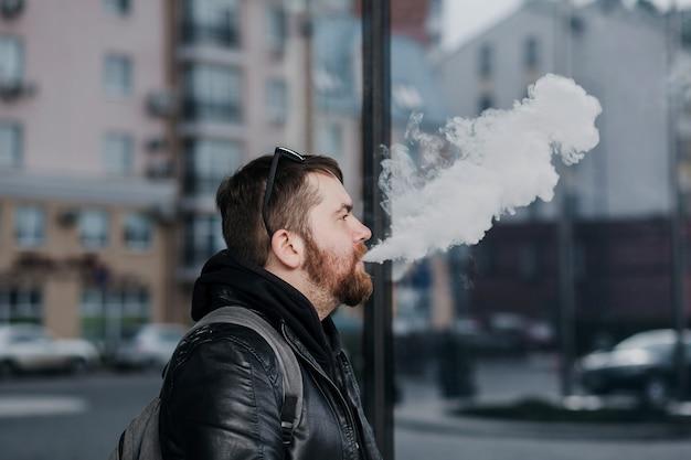 Un bell'uomo con uno zaino in giacca di pelle fuma in città