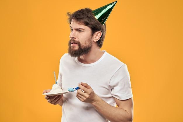 Uomo bello con la barba e in un berretto che celebra uno sfondo giallo festa di compleanno.