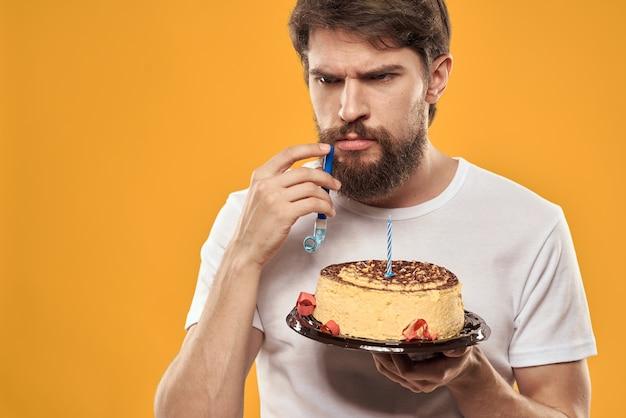 Uomo bello con la barba che celebra una festa di compleanno su uno sfondo giallo.