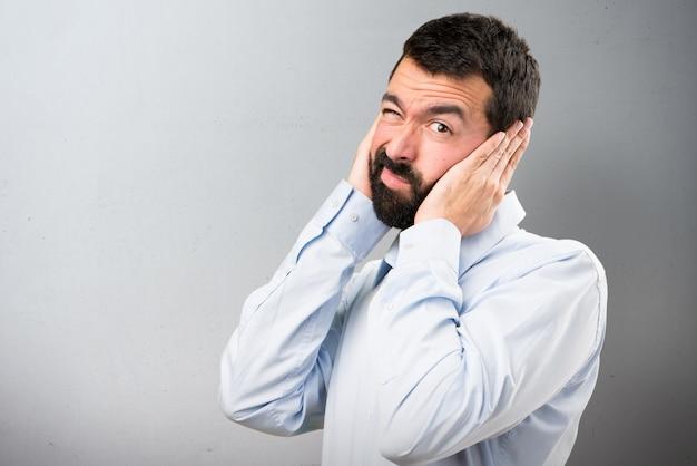 Uomo bello con la barba che copre le orecchie su sfondo testurizzato