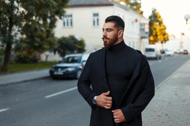 Bell'uomo con barba e acconciatura in un elegante cappotto nero cammina per strada