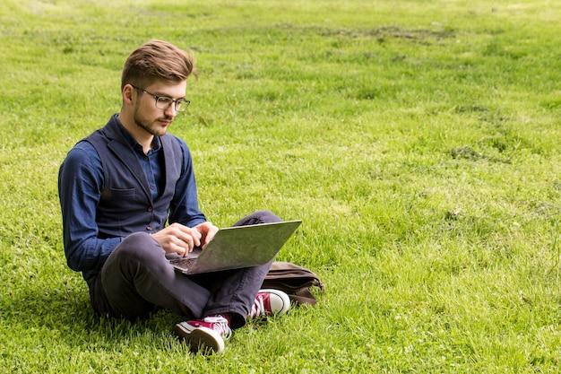 Un bell'uomo con la barba è seduto su un prato e lavora su un laptop