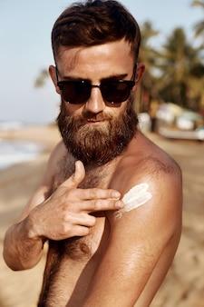 Uomo bello con la barba, in occhiali da sole, prendere il sole con crema solare corpo in estate.