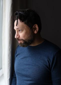 Bell'uomo con la barba sorpreso guardando la finestra, faccia maschile felice emotiva al coperto
