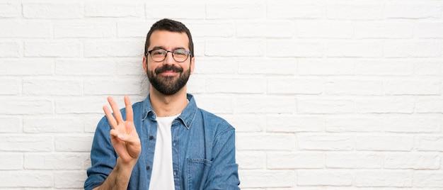 Uomo bello con la barba sopra il muro di mattoni bianco felice e contando tre con le dita