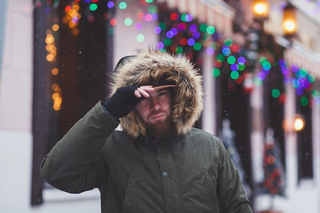 Uomo bello con la barba in un cappotto invernale che cammina per strada