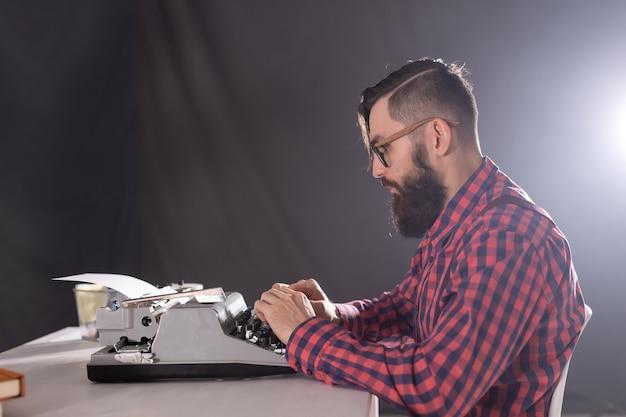 Uomo bello con la barba che lavora alla macchina da scrivere