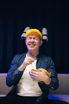 Uomo bello con casco di birra sulla testa guardando la tv e mangiare patatine sul divano a casa