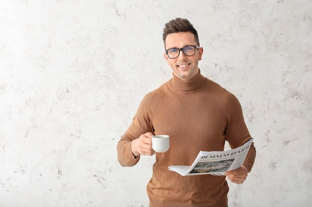 Uomo bello con caffè e giornale sulla superficie chiara
