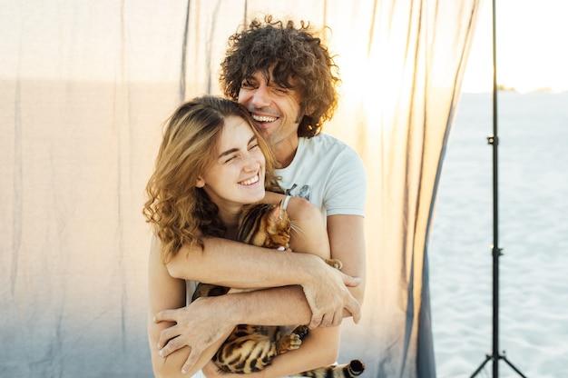 Un bell'uomo con i capelli ricci abbraccia dolcemente la sua amata. hanno un gatto tra le mani