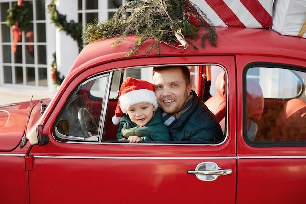 Uomo bello con il neonato sveglio in cappello di babbo natale all'interno dell'auto retrò rossa con regali di natale