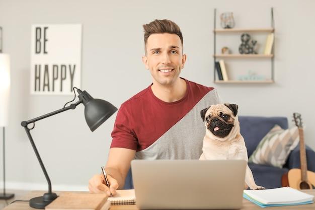 Uomo bello con cute pug cane e laptop a casa