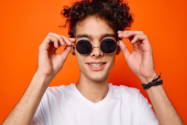 Uomo bello con i primi piani di moda degli occhiali da sole dei capelli della legna da ardere
