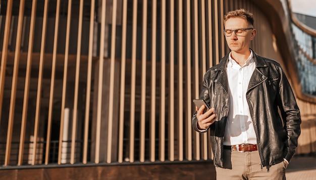 Bell'uomo con gli occhiali con uno smartphone sulla strada di una grande città. uomo d'affari che parla al telefono sullo sfondo urbano