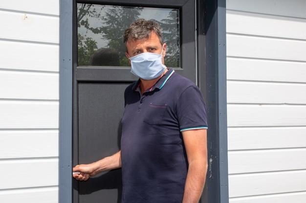 Uomo bello con la maschera protettiva anteriore porta di casa confinata in quarantena durante l'epidemia di coronavirus covid-19