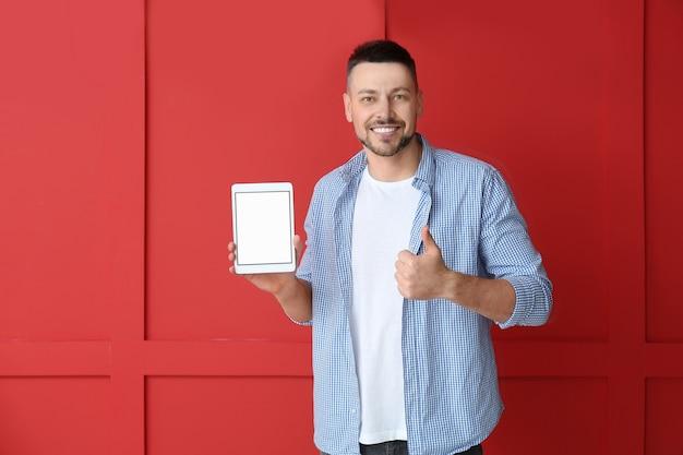Bell'uomo con computer tablet che mostra pollice in su su sfondo a colori