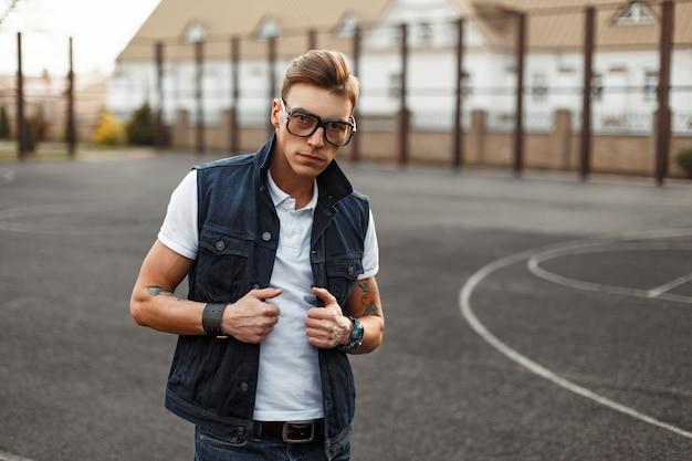 Bell'uomo con occhiali vintage che indossa una camicia bianca e un gilet di jeans