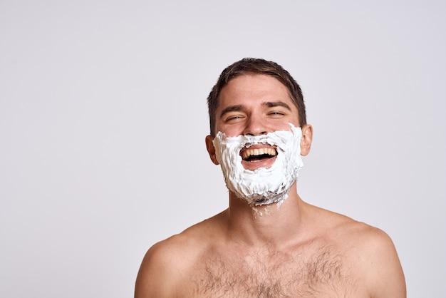 Uomo bello con schiuma da barba bianca sul viso e pelle pulita con il rasoio che cura le spalle nude