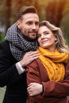 Bell'uomo e una donna abbracciati da dietro sorridono guardandosi l'un l'altro nel parco in autunno