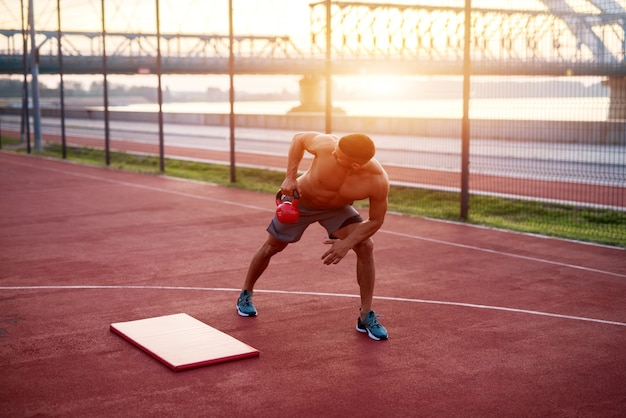 Bell'uomo esercizi di lavoro al mattino presto con l'alba. allenamento fitness all'aperto.