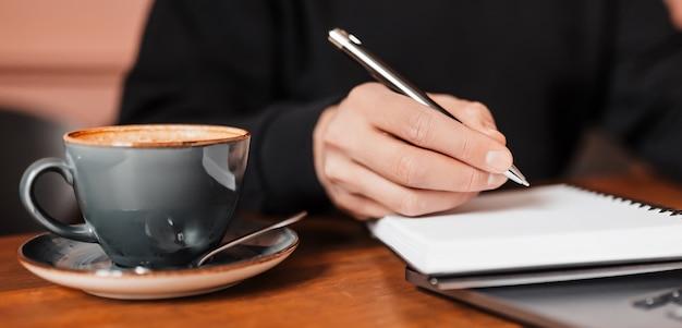 Uomo bello che lavora al computer portatile sul posto di lavoro. imprenditore digitando informazioni sul computer al tavolo di lavoro con caffè e blocco note