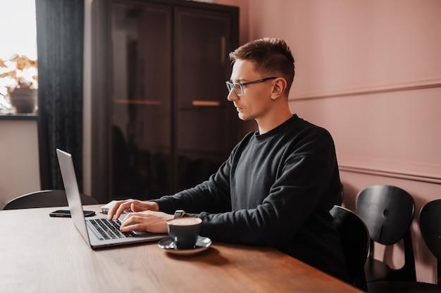 Uomo bello che lavora al computer portatile sul posto di lavoro
