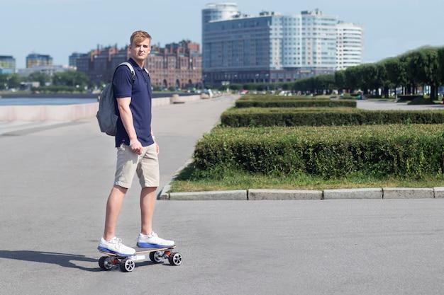 Uomo bello, giovane ragazzo su uno skateboard elettrico moderno o longboard a cavallo in città con zaino al giorno d'estate. tecnologia, gadget, concetto di trasporto.