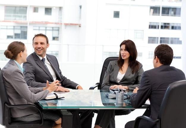 Bello manager ridere durante una riunione con la sua squadra