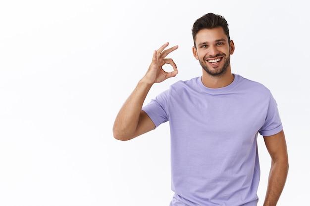 Bel maschio sorridente, uomo incoraggiato con le setole, indossa una maglietta viola, mostra un gesto ok, buono o eccellente, fa il segno ok e sorride con approvazione, dà un feedback positivo, muro bianco