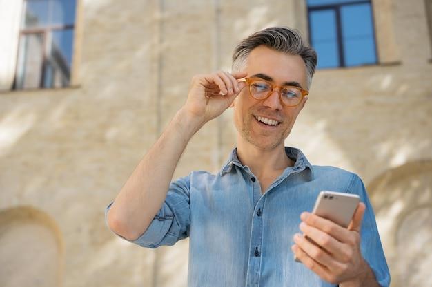 Uomo d'affari maturo bello che tiene smartphone, comunicazione, lettura di notizie.
