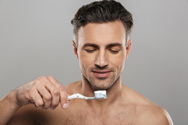 Uomo maturo bello che pulisce i suoi denti.