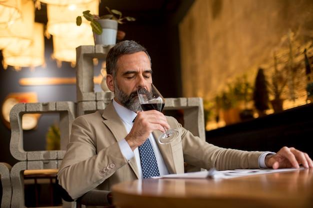 Bicchiere bello dell'uomo maturo di vino rosso in ristorante