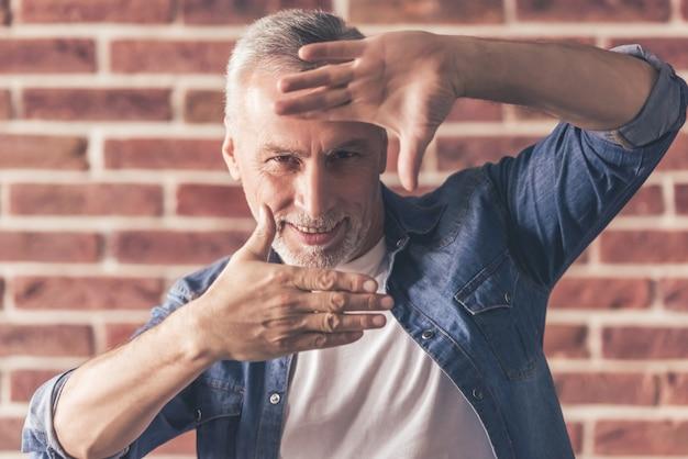 L'uomo maturo bello sta facendo una struttura della mano.