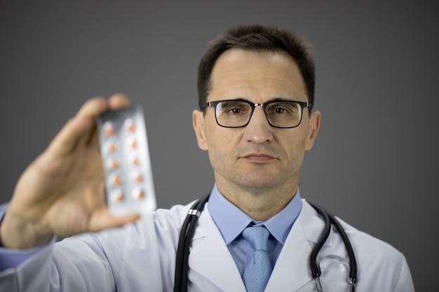 Il medico maschio di mezza età bello in vetri mostra con sicurezza le pillole di prescrizione isolate sul muro grigio