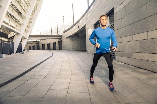 Un bell'uomo serio di mezza età in uniforme sportiva nera blu e cuffie e fitness tracker è in esecuzione in città.