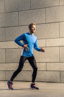 Un bell'uomo serio di mezza età in uniforme sportiva nera blu e cuffie e fitness tracker è