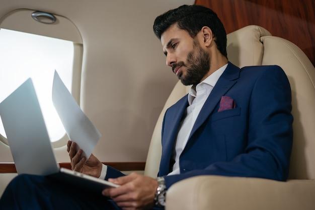 Bello uomo d'affari mediorientale che utilizza laptop per leggere report finanziarivolare un jet privato di lusso