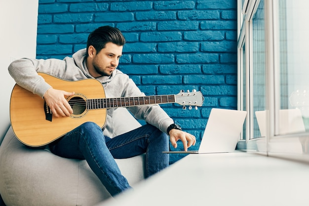 Bello millenial holding chitarra e utilizzando il suo laptop alla finestra in camera moderna, copia dello spazio