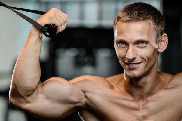 Armi di modello belle di addestramento del giovane in palestra