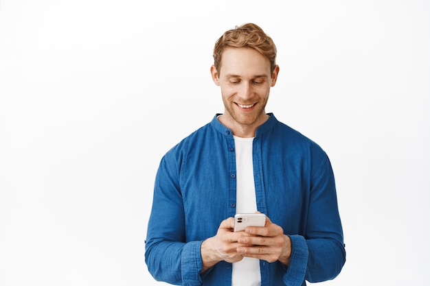 Bel ragazzo moderno con messaggi di capelli rossi, leggendo lo schermo su smartphone, chattando e sorridendo, facendo ordini di shopping online sul telefono, in piedi sul muro bianco