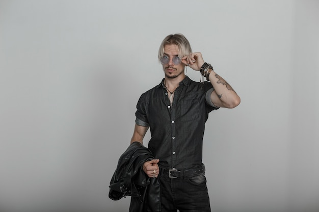 Uomo bello e moderno giovane hipster in vestiti alla moda in denim nero con tatuaggi in vetri blu vintage in posa in studio vicino al muro.