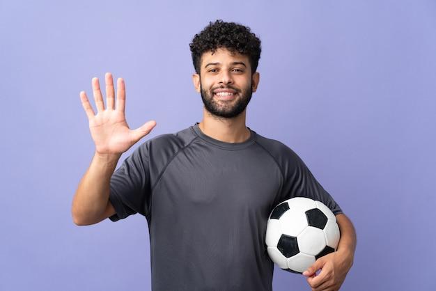 Bel giovane calciatore marocchino uomo sopra isolato su viola contando cinque con le dita