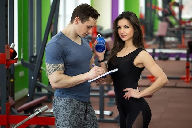 Istruttore maschio muscoloso bello che consulta femmina giovane attraente in palestra, entrambi sorridenti