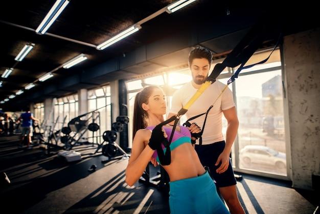 Allenatore barbuto muscoloso bello allenamento con ragazza di forma durante l'allenamento in palestra.